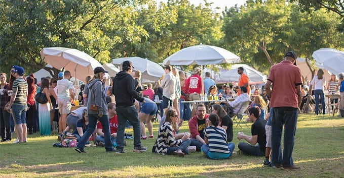 People chowing down under umbrellas at Taste of Addison